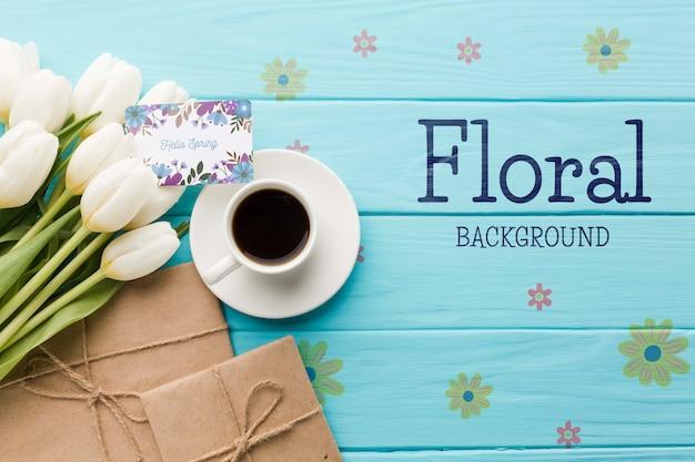 Plat leggen van koffiekopje met tulpen en geschenken Gratis Psd
