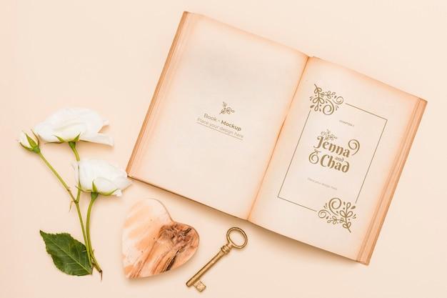 Plat leggen van open boek met rozen en sleutel Gratis Psd