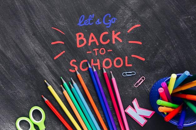Plat terug naar school met kleurrijke benodigdheden Gratis Psd