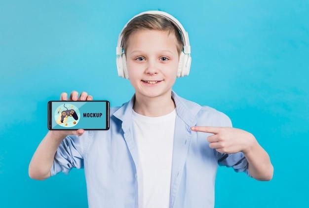 Portret van de jonge telefoon van de jongensholding met model Gratis Psd