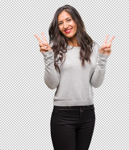 Portret van jonge indiase vrouw plezier en gelukkig, positief en natuurlijk, het doen van een gebaar van de overwinning, vrede concept Premium Psd