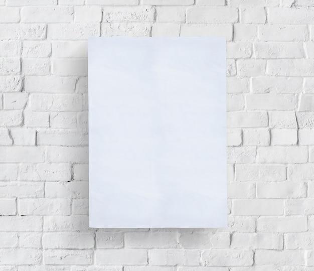 Poster bianco davanti al muro di mattoni Psd Gratuite