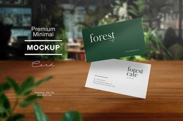 Premium schoon minimaal visitekaartje mockup op houten tafel in bos café en lichte schaduw. Premium Psd
