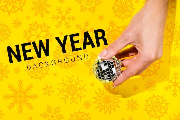 Priorità bassa di nuovo anno con la mano che tiene una sfera di natale Psd Gratuite
