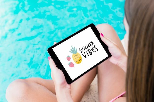 Ragazza che presenta tablet mockup accanto alla piscina Psd Gratuite