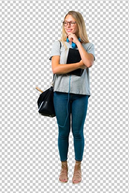 Ragazza studentessa con gli occhiali in piedi e guardando al lato con la mano sul mento Psd Premium