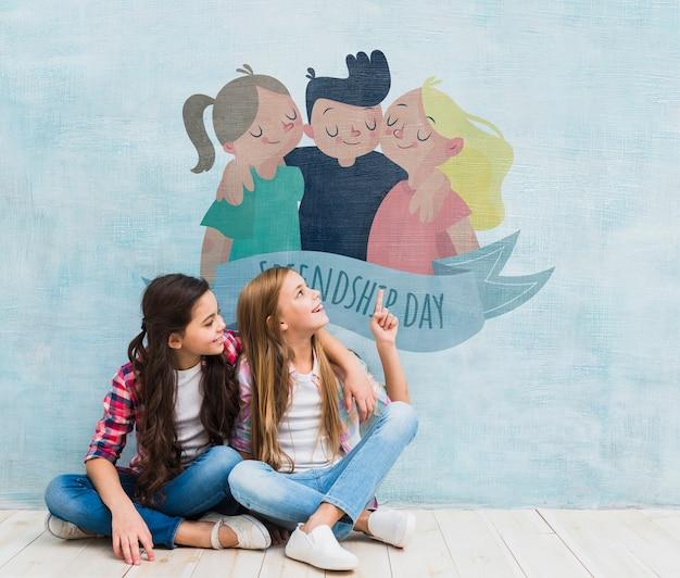Ragazze di fronte a un muro con un cartone animato mock-up Psd Gratuite