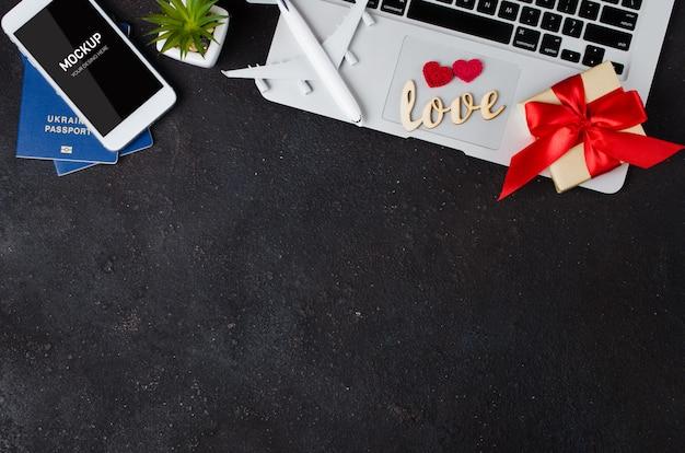 Reisplanning met smartphone, vliegtuigmodel, laptop, paspoorten en geschenkdoos Premium Psd