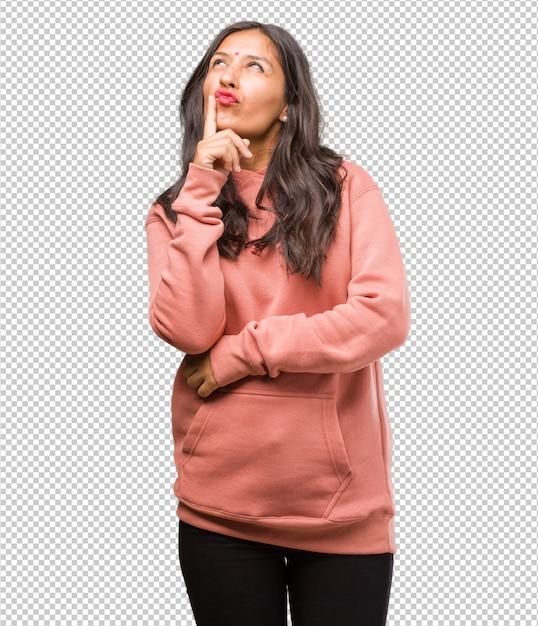 Ritratto di fitness giovane donna indiana, pensando e alzando lo sguardo, confuso su un'idea Psd Premium