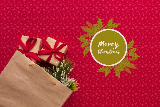 Sacco di carta in pieno dei regali sul fondo di rosso di natale Psd Gratuite