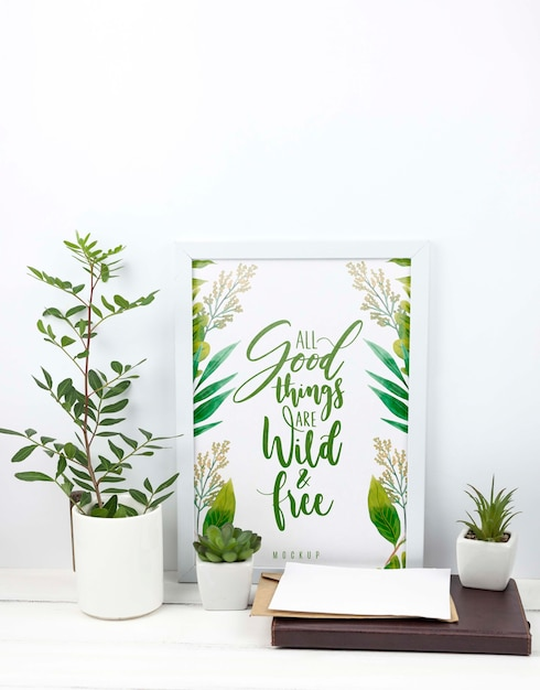 Samenstelling van planten naast frame mockup Gratis Psd