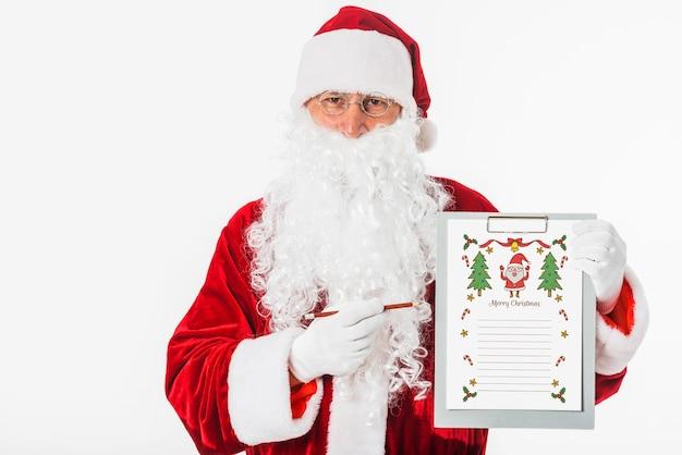 Santa tenendo appunti con wishlist Psd Gratuite