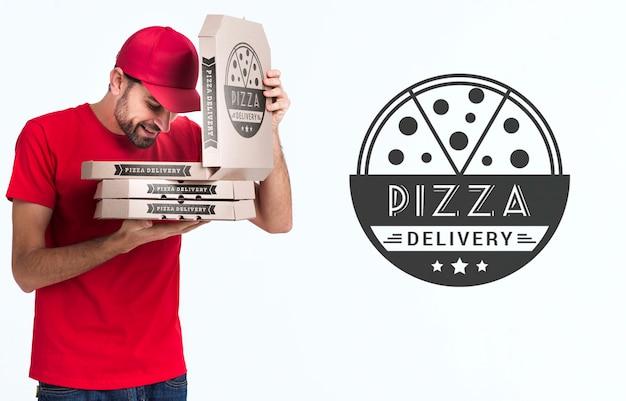 Scatole della tenuta del ragazzo della pizza e guardare in uno di loro Psd Gratuite