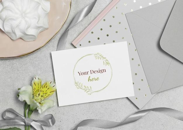 Scheda del modello con fiore, marshmallow e nastro su sfondo grigio Psd Premium