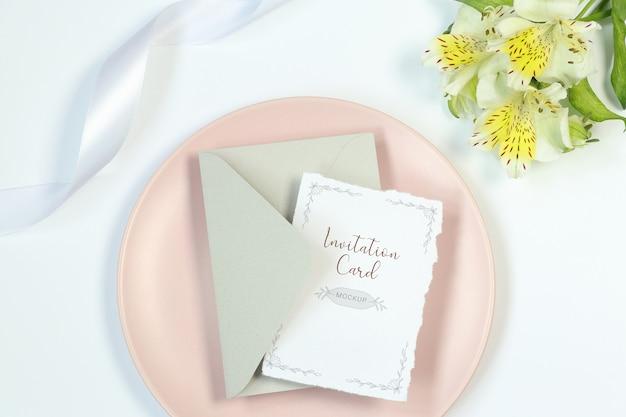 Scheda dell'invito del modello su priorità bassa bianca con fiori, busta grigia e nastro Psd Premium