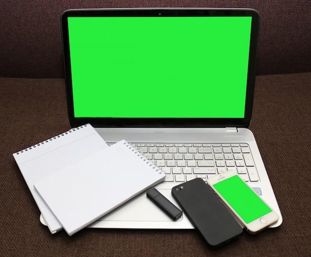 Schermo del computer portatile verde e smartphone con il blocco note a spirale e flash drive Psd Gratuite