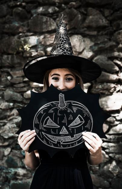 Schets van een gesneden pompoen en een vrouw gekleed als een heks Gratis Psd