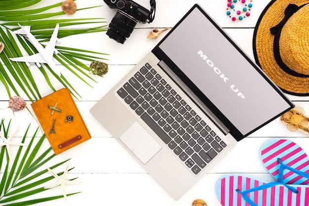 Simulacros de pantalla de laptop en mesa de madera blanca para vacaciones de verano PSD Premium
