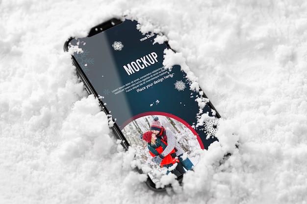 Sluit omhoog smartphone in sneeuw Gratis Psd