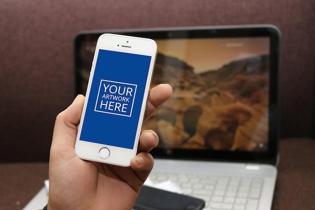 Smartphone met groen scherm in de hand met laptop achtergrond Gratis Psd