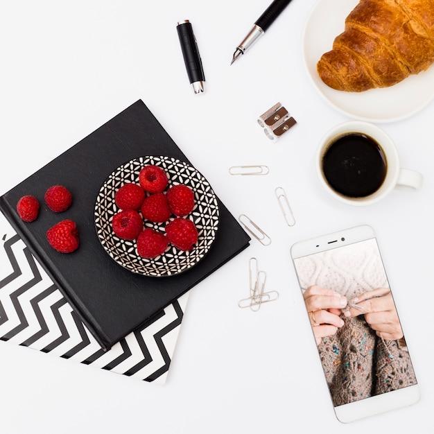 Smartphone-mockup met ontbijt op kantoor Gratis Psd