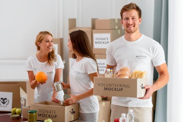 Smiley-vrijwilligers maken provisieboxen klaar voor donatie Gratis Psd