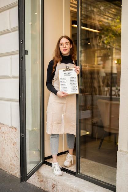 Smileyvrouw die bij een restaurant werkt dat een menu houdt Gratis Psd