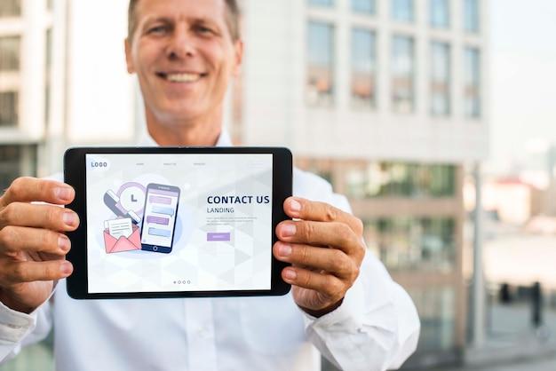 Smileyzakenman die in openlucht horizontale digitale tablet houden Gratis Psd