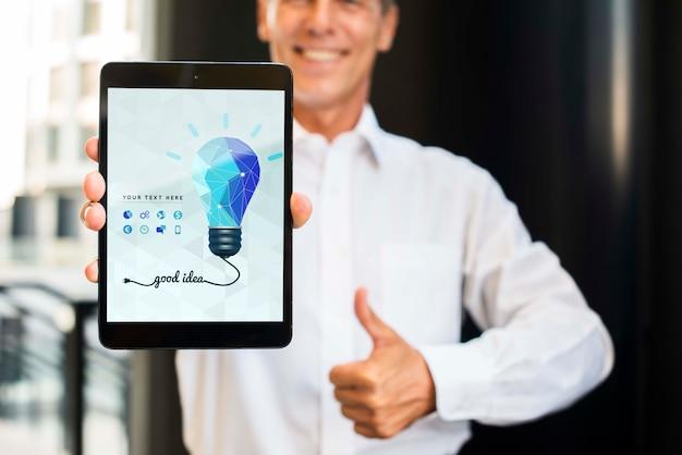 Smileyzakenman die in openlucht verticale digitale tablet houden Gratis Psd