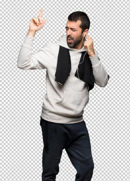 Sport man luisteren naar muziek met een koptelefoon en dansen Premium Psd