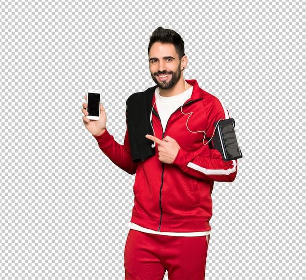 Sportivo bello felice e indicando il cellulare Psd Premium