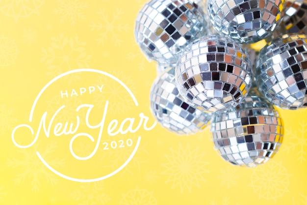 Stapel zilveren kerstballen op gele nieuwe jaarachtergrond Gratis Psd