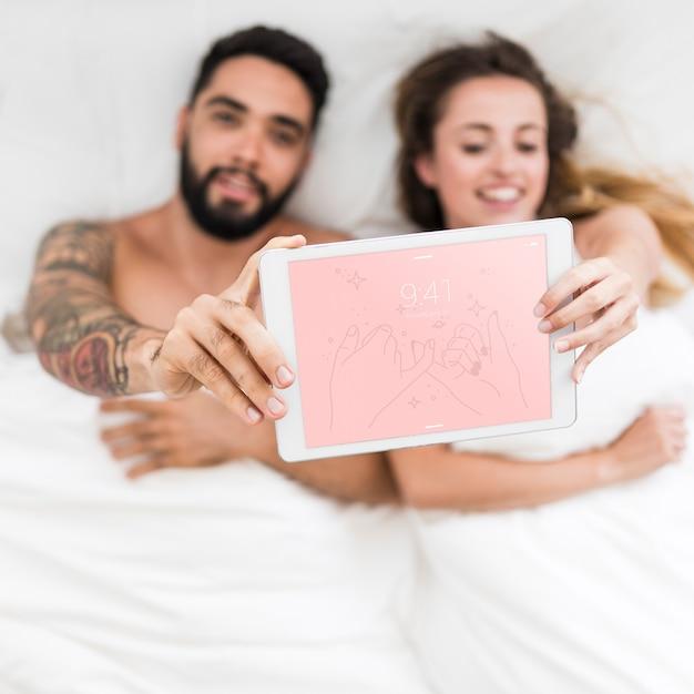 Tabletmodel met paar in bed Gratis Psd