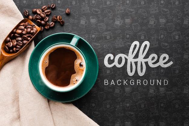 Taza de café y cuchara de madera con fondo de granos de café PSD Premium