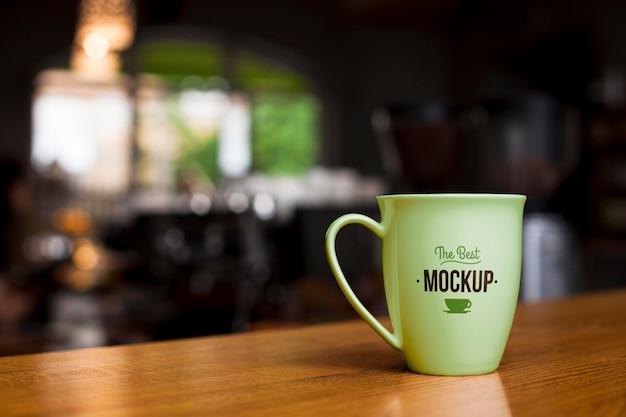 Taza de café verde en la mesa de madera PSD gratuito