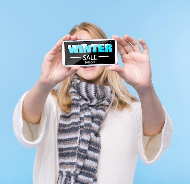Telefono della tenuta della giovane donna con il modello Psd Gratuite