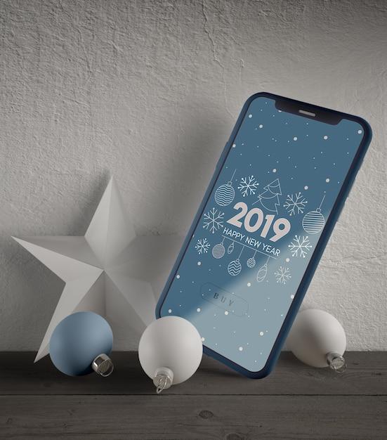 Telefoon met kerstthema en decoraties naast Gratis Psd
