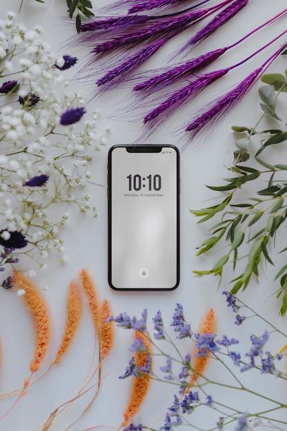 Telefoonmodel omlijst met een stel gedroogde, kleurrijke bloemen Premium Psd
