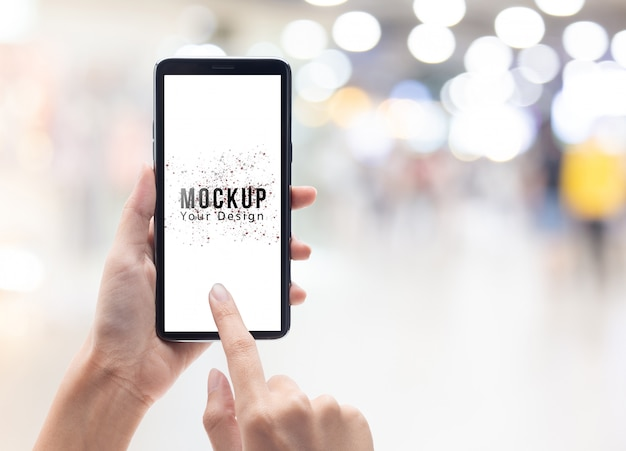 Tenuta della mano della donna e smartphone nero commovente con il modello del modello dello schermo in bianco Psd Premium