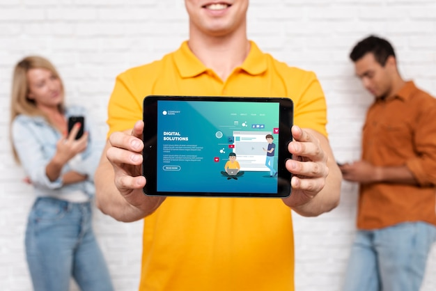Texto de soluciones digitales en tableta con personas desenfocadas en segundo plano PSD gratuito