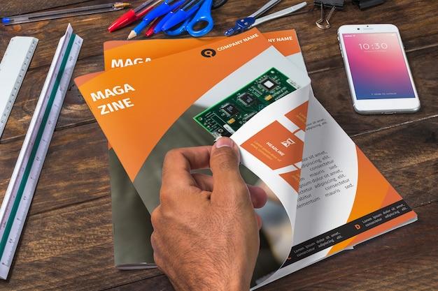 Tijdschrift en smartphone mockup op houten tafel met pennen en linialen Gratis Psd