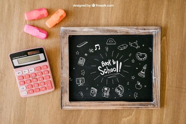 Torna alla composizione scolastica con ardesia e calcolatrice su superficie in legno Psd Gratuite