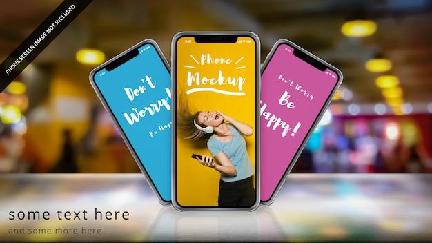Tre apple iphone x su una superficie riflettente con bokeh Psd Premium