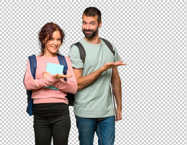 Twee studenten met rugzakken en boeken die een idee voorstellen terwijl het kijken glimlachen naar Premium Psd