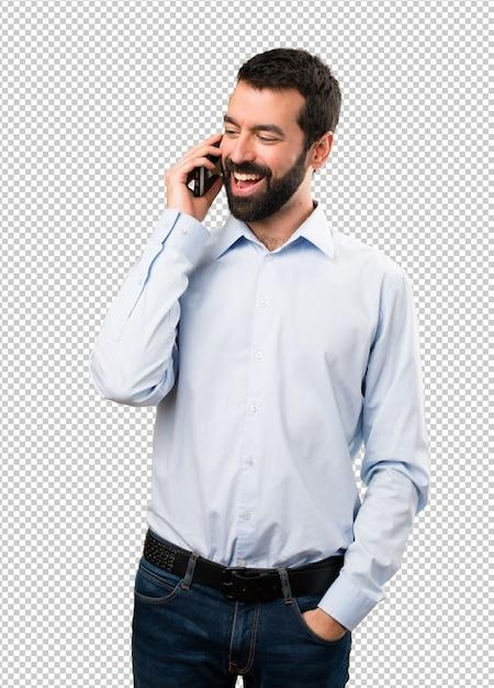 Uomo bello felice con la barba che comunica con mobile Psd Premium