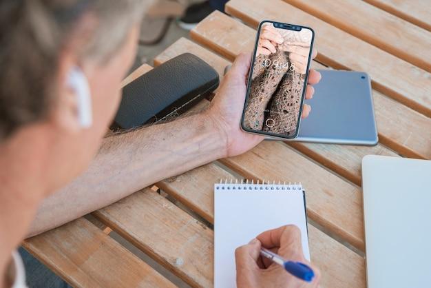 Uomo che guarda il mockup di smartphone Psd Gratuite