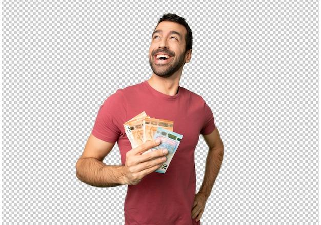 Uomo che prende un sacco di soldi in posa con le braccia all'anca e ridendo Psd Premium