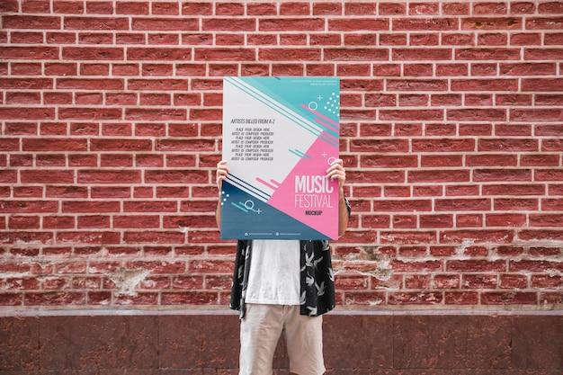Uomo che presenta il poster mockup davanti al muro di mattoni Psd Gratuite