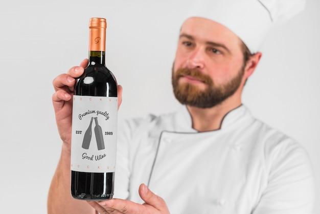 Uomo che presenta la bottiglia di vino Psd Gratuite