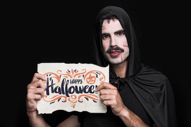 Uomo che tiene la carta con lettering di halloween Psd Gratuite